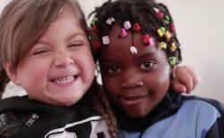dos estudiantes de educación básica de diferente nacionalidad abrazándose y sonriendo a la cámara.